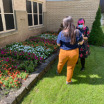 Two KaBloom judges look at red, pink, and white flower beds