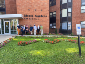 """Group photo of KaBloom judges in front of Morse Gardens with flowers planted in the shape of an """"M"""" in the front lawn"""