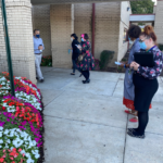 KaBloom judges inspect red, white, and pink flowers in front of building