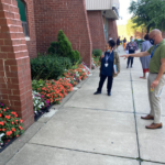 Judges stand on the sidewalk and look at flowers planted at foot of building